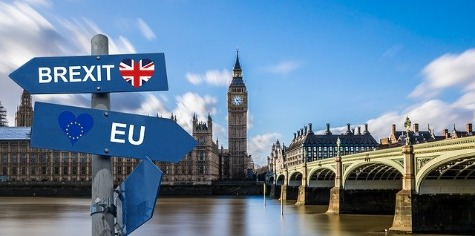 Brexit later led to a Coalition Chaos with chaotic negotiation. UK Houses of Parliament shown behind a Brexit sign.