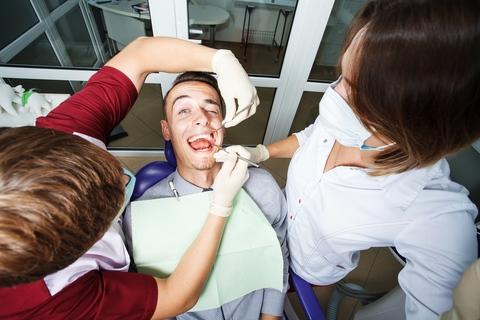 dentist-examining-dental-patient-teeth